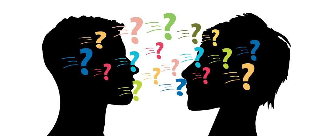 Die Silhouette zweier Köpfe, die einander zugewandt sind. Zwischen ihnen schweben bunte Fragezeichen hin- und her.