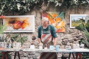 älterer Maler steht vor Tapeziertisch mit Farben - hinter ihm an der Steinwand befinden sich abstrakte Bilder