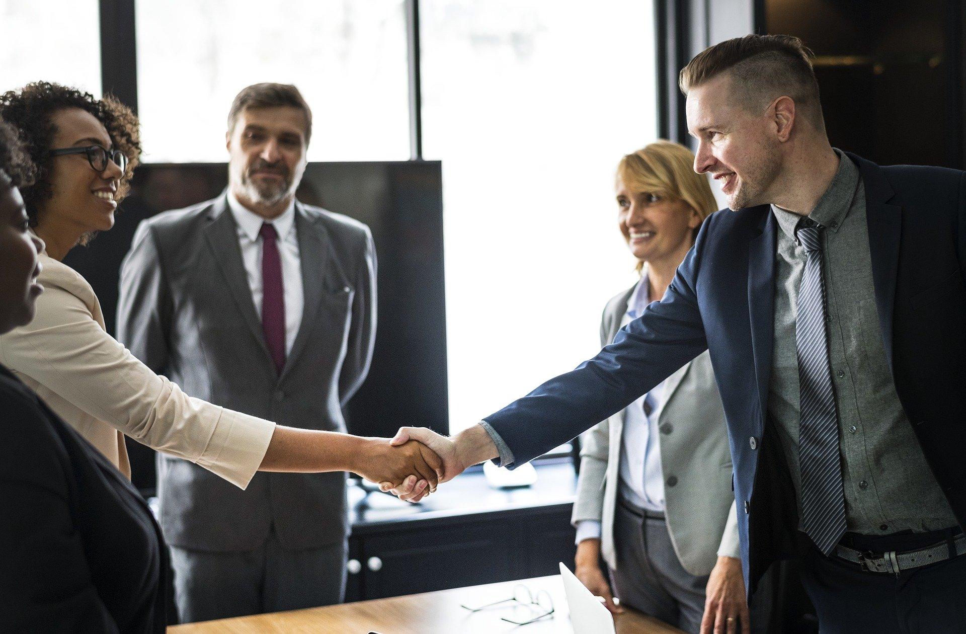 Eine Gruppe Menschen im Business-Kontext schauen zu, wie begeistert zwei mit einen Handschlag etwas besiegeln.