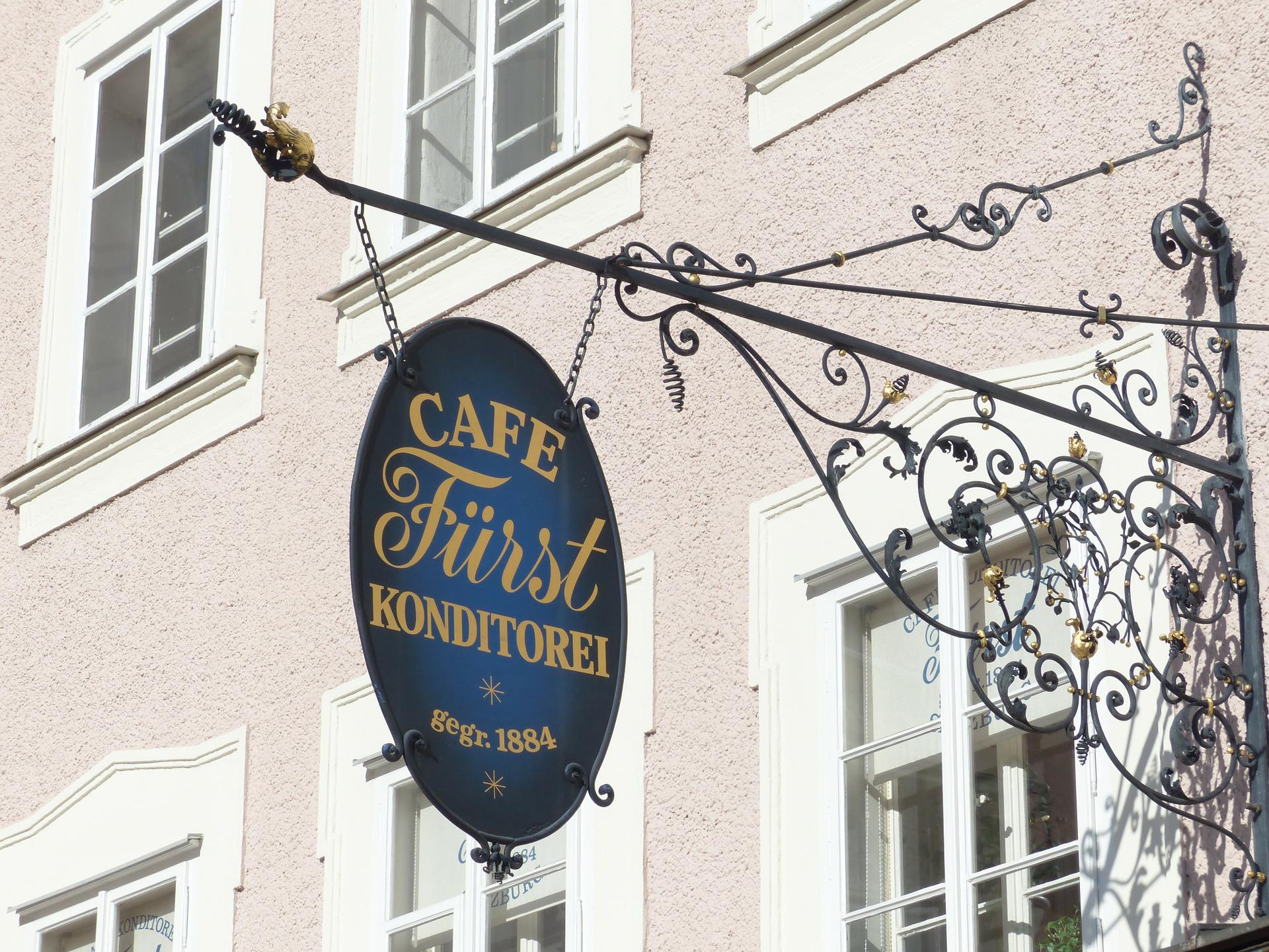 Von einem Haus hängendes schmiedeeisernes Türschild eines Cafés
