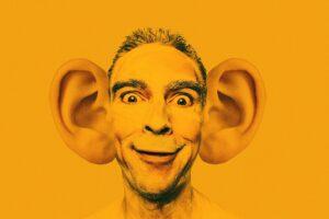 Männergesicht mit riesigen Ohren als Fotomontage vor orangefarbenem Hintergrund