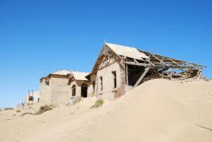Verfallene Häuser auf einer Düne in der Wüste