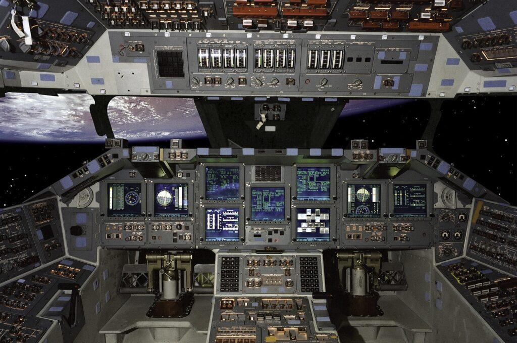 Cockpit eines Space Shuttles - überwältigend viele Anzeigen und Regler, im Hintergrund ist kopfüber die Erde zu sehen