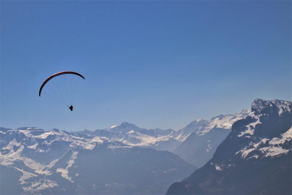 Gleitschirmflieger über dem schneebedeckten Alpenpanorama