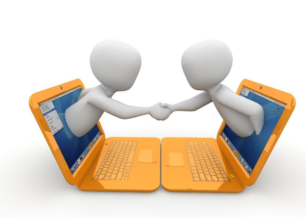 Zwei Männchen klettern aus jeweils gegenüberliegenden Laptop-Bildschirmen und reichen sich die Hand