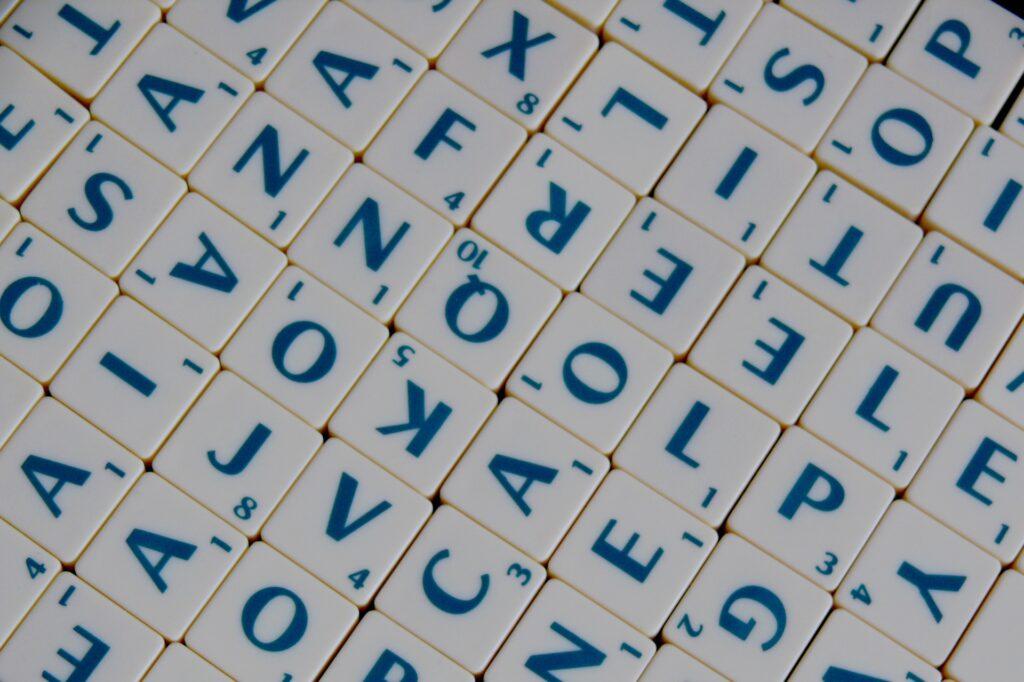 Viele verschiedene Buchstaben auf Scrabblesteinen wahllos direkt aneinandergelegt